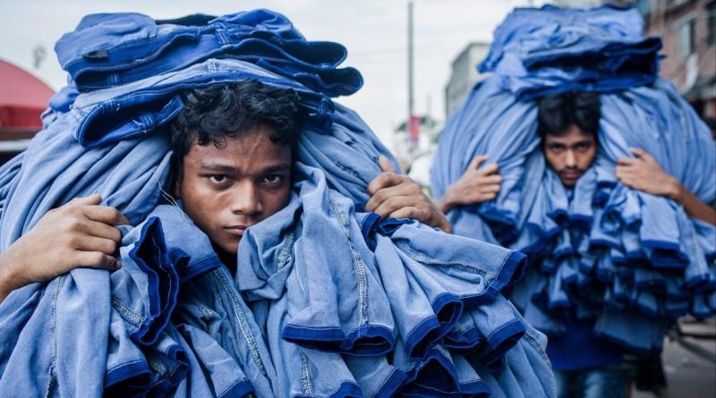 """""""Trabalhadores"""" mostra dois trabalhadores da indústria têxtil transportando ganga no Bangladesh. A imagem ganhou a categoria das """"13h00"""""""