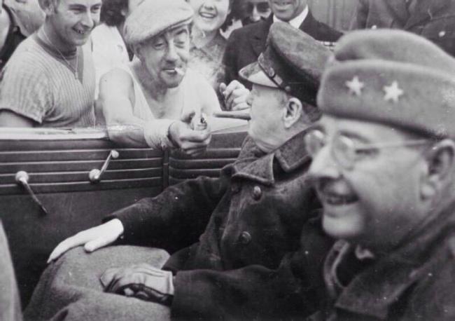 Um francês acende o charuto de Winston Churchill, 1944.