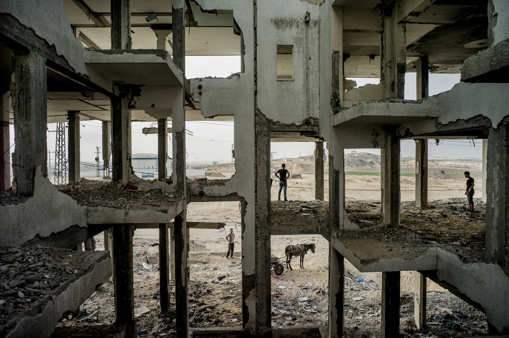 BEIT LAHIYA, GAZA 8/3/2015 People looked for concrete to salvage in a building destroyed by the 2014 war between Israel and Palestinian militants in Gaza. Tomas Munita for The New York Times