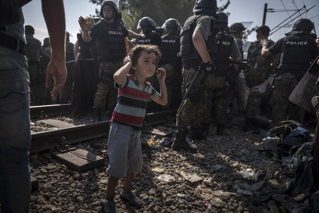 GREECE-MACEDONIA BORDER, NEAR IDOMENI, GREECE 8/26/2015 A child stood near police controlling a rush of refugees into Macedonia. Sergey Ponomarev for The New York Times