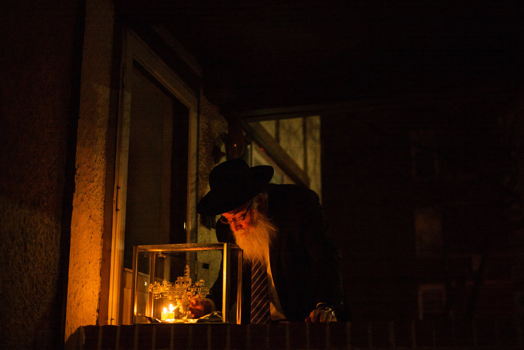 BROOKLYN, N.Y. 12/7/2015 Leib Kelman lit candles on a menorah for Hanukkah outside his home in the Kensington neighborhood. Todd Heisler/The New York Times