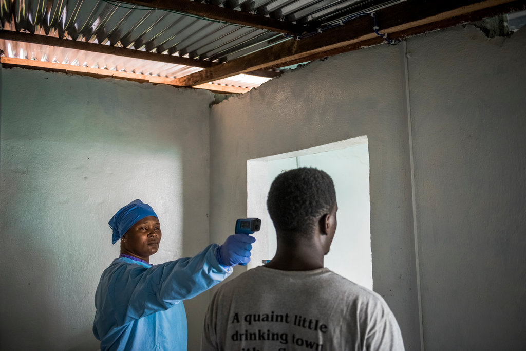 MONROVIA, LIBERIA 2/18/2015 A nurse used an infrared thermometer to check a patient's temperature at the Logan Town Health Clinic. The World Health Organization declared the nation free of Ebola in May. Daniel Berehulak for The New York Times