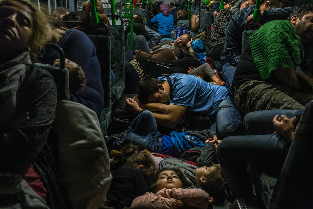 BUDAPEST, HUNGARY 9/5/2015 A Syrian father, center, slept with his son and other family members on the floor of a bus driving from Budapest to Vienna. Mauricio Lima for The New York Times