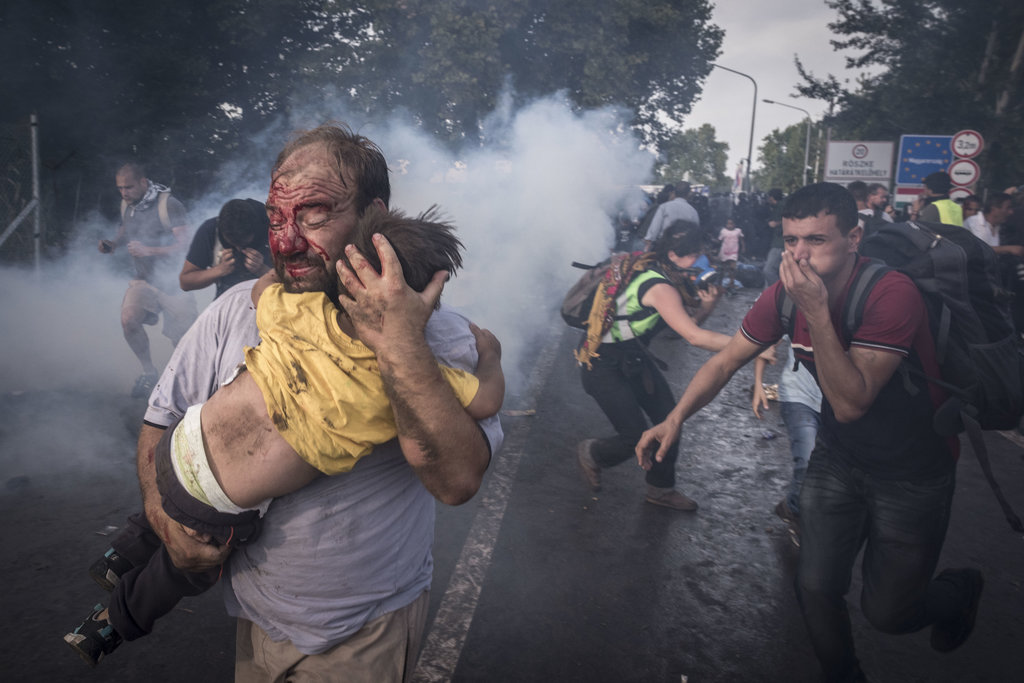 HUNGARY-SERBIA BORDER, NEAR HORGOS, SERBIA 9/16/2015 A man tried to save his child as Hungarian police officers fired tear gas, pepper spray and water cannons at migrants trying to cross into the country. Sergey Ponomarev for The New York Times