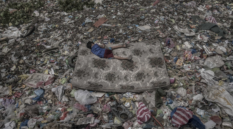 A child who collects recyclable materials lying in a mattress surrounded by a garbage patch floating on the Pasig River in Manila, Philippines, October 2018. In some parts of the river the waste is so dense that is possible to walk on top of the garbage.