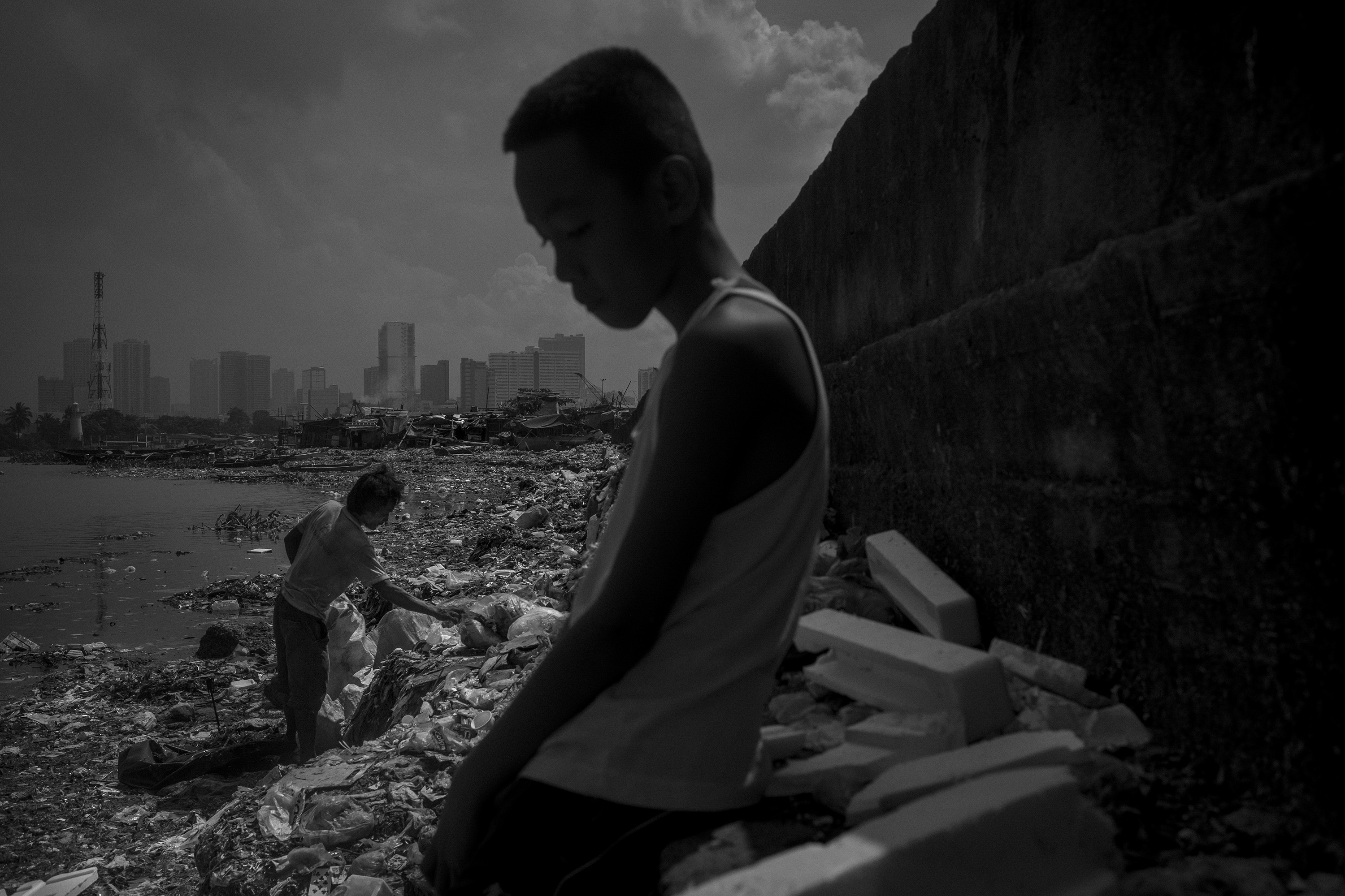 Arjay Onbrog looks to domestic waste in Pasig River as Hilario Bomong tries to collect recyclables in Baseco, Manila, Philippines, September 2018. At the Port area is the well-known Baseco compound, where thousands of families are out of sight of those who live every day in Metro Manila. From Baseco it's possible to see a garbage patch running along the bank, collectors are as natural as the pollution.